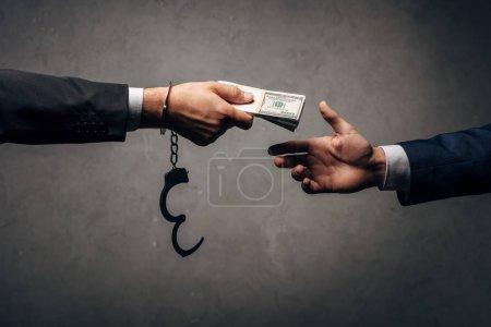 Photo pour Vue recadrée homme d'affaires menotté donnant pot de vin à un partenaire d'affaires sur gris - image libre de droit
