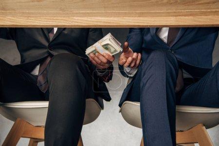 Photo pour Homme d'affaires de vue recadrée donnant le pot-de-vin à l'associé d'affaires tout en s'asseyant sur la présidence - image libre de droit