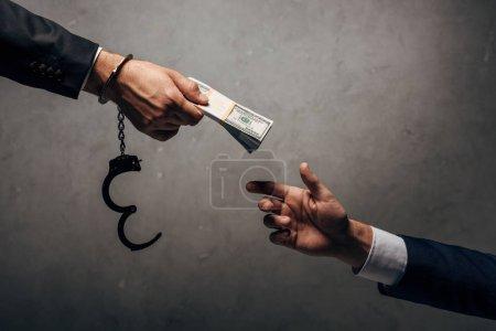Photo pour Vue recadrée homme menotté donnant pot de vin à un partenaire d'affaires sur gris - image libre de droit