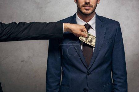 Photo pour Vue recadrée de l'homme mettant le pot-de-vin dans la poche du associé d'affaires sur le gris - image libre de droit