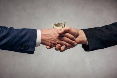 Photo pour Homme recadré de vue serrant la main avec le associé tout en donnant l'argent sur le gris - image libre de droit