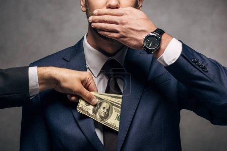 Photo pour Vue recadrée de l'homme mettant l'argent comptant dans la poche de la couverture d'homme d'affaires le visage sur le gris - image libre de droit