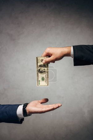 Photo for Cropped view man taking bribe near business partner on grey - Royalty Free Image