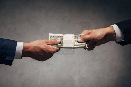 Foto de Recortado ver a hombre de negocios tomando soborno cerca de socio de negocios en gris - Imagen libre de derechos