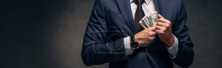 panoramic shot of businessman in suit putting cash in pocket on grey