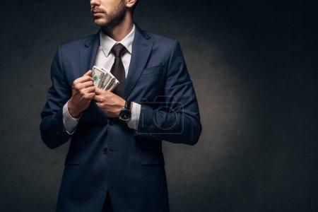 Photo pour Vue recadrée de l'homme d'affaires mettant l'argent comptant dans la poche sur le noir - image libre de droit