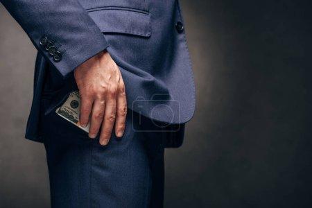 Photo pour Vue recadrée de l'homme d'affaires restant et mettant des billets de banque de dollar dans la poche sur le gris - image libre de droit