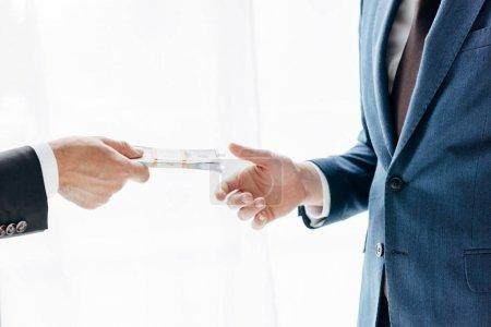 Photo pour Vue recadrée de l'homme donnant de l'argent au partenaire d'affaires sur blanc - image libre de droit