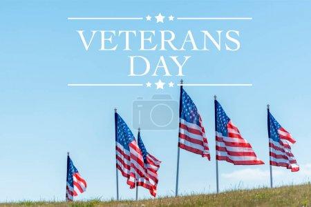 Photo pour Drapeaux américains nationaux sur l'herbe verte contre le ciel bleu avec l'illustration de jour d'anciens combattants - image libre de droit