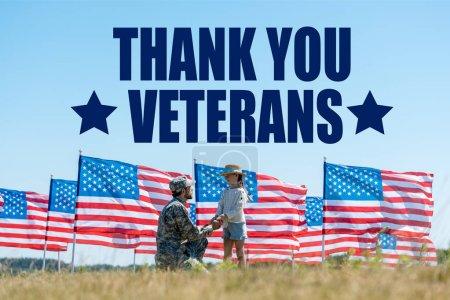 Photo pour Foyer sélectif du père militaire retenant des mains avec le gosse mignon près des drapeaux américains avec l'illustration de vétérans de remerciement - image libre de droit