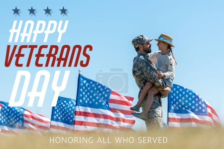 Photo pour Selective focus of man in military uniform holding in arms cheerful kid near american flags with happy veterans day, honoring all who served illustration - image libre de droit