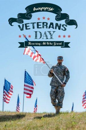 Foto de Apuesto soldado en uniforme militar y gorra sosteniendo la bandera americana con feliz día de veteranos, honrando a todos los que sirvieron ilustración - Imagen libre de derechos