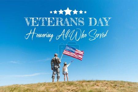 Photo pour Vue arrière de l'enfant dans le chapeau de paille et le père militaire retenant des drapeaux américains avec le jour d'anciens combattants, honorant tous ceux qui ont servi l'illustration - image libre de droit