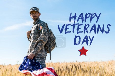 Photo pour Soldier in uniform holding american flag while standing in field with happy veterans day illustration - image libre de droit