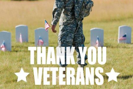 Photo pour Vue recadrée de l'homme militaire retenant le drapeau américain près des pierres tombales dans le cimetière avec l'illustration de vétérans de remerciement - image libre de droit
