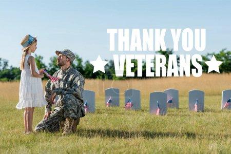 Photo pour Homme militaire dans le chapeau s'asseyant près de l'enfant dans le chapeau de paille et les pierres tombales dans le cimetière avec l'illustration de vétérans de remerciement - image libre de droit