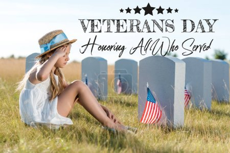 Photo pour Kid in straw hat giving salute while sitting near headstones with american flags with veterans day, honoring all who served illustration - image libre de droit