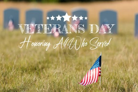 Photo for Selective focus of american flag with stars and stripes near gravestones with veterans day, honoring all who served illustration - Royalty Free Image