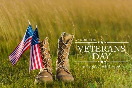Photo pour Bottes militaires près du drapeau américain avec des étoiles et des rayures sur l'herbe avec l'illustration de jour d'anciens combattants - image libre de droit