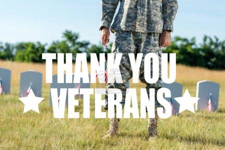 Foto de Vista recortada de soldado en uniforme de camuflaje sosteniendo la bandera americana y de pie en el cementerio con la ilustración de los veteranos gracias - Imagen libre de derechos