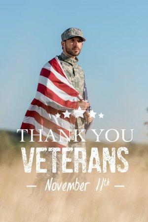 Foto de Enfoque selectivo del hombre en uniforme de camuflaje y gorra sosteniendo la bandera americana en el campo de oro con gracias veteranos ilustración - Imagen libre de derechos