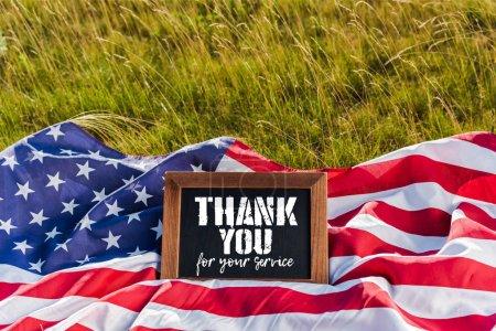 Photo pour Tableau noir avec merci pour votre illustration de service sur drapeau américain avec des étoiles et des rayures sur herbe verte - image libre de droit