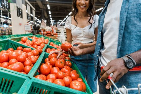 Photo for Cropped view of cheerful woman neat african american man holding tomato - Royalty Free Image