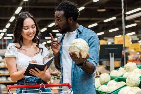 Photo for African american man gesturing and holding cabbage near asian cheerful woman with notebook - Royalty Free Image
