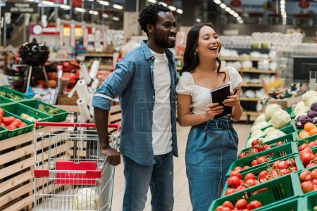 Photo for Cheerful african american man near attractive asian woman holding notebook in supermarket - Royalty Free Image