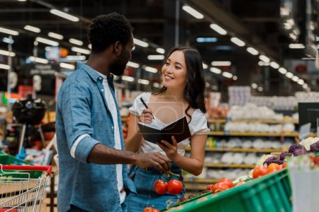 Photo pour Homme américain africain retenant les tomates fraîches et regardant la femme asiatique heureuse avec le cahier et le stylo - image libre de droit