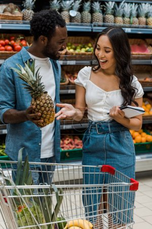 Photo for Cheerful asian girl with notebook gesture while looking at pineapple near african american man - Royalty Free Image