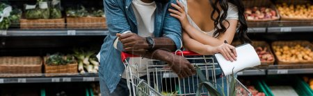 Photo for Panoramic shot of african american man and woman standing near shopping cart in supermarket - Royalty Free Image