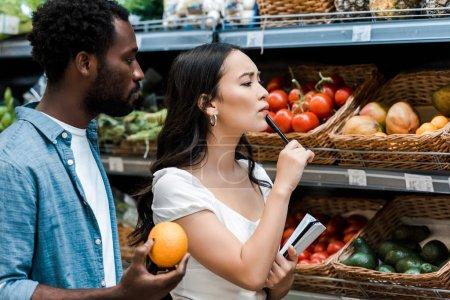 Foto de Mujer asiática pensativa con pluma de pie cerca de frutas y hombre afroamericano con naranja - Imagen libre de derechos