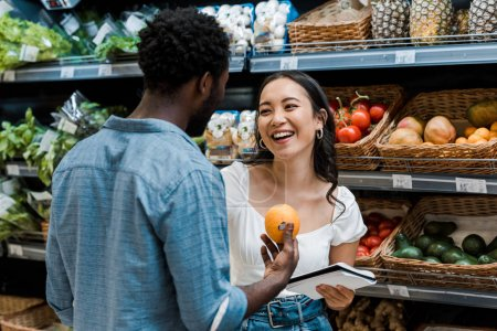 Photo for Cheerful asian girl near african american man with orange in store - Royalty Free Image