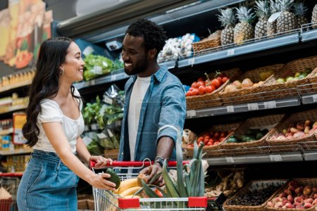 Photo for Happy asian girl holding avocado near shopping cart and african american man in store - Royalty Free Image