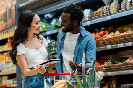 Photo for Selective focus of happy african american man gesturing and looking at asian girl holding notebook in store - Royalty Free Image