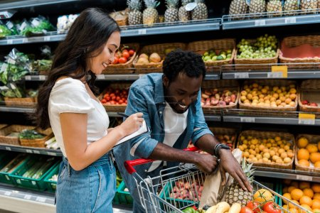 Photo for Happy african american man looking at shopping cart with groceries near cheerful asian woman with notebook - Royalty Free Image