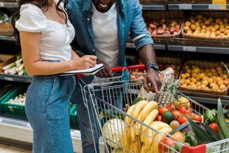 Photo for Cropped view of happy african american man pointing with finger at shopping cart with groceries near woman with notebook - Royalty Free Image