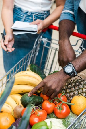 Photo for Selective focus of african american man pointing with finger at shopping cart with groceries near woman with notebook - Royalty Free Image