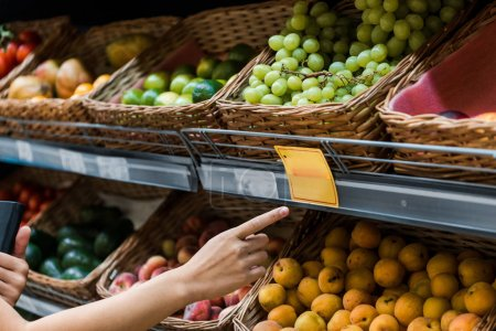Photo for Selective focus of woman pointing with finger at fruits in supermarket - Royalty Free Image