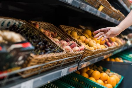 Photo for Cropped view of young woman near fruits in supermarket - Royalty Free Image
