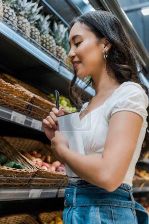 Photo pour Faible angle vue de heureux asiatique fille tenant carnet et stylo près de fruits dans supermarché - image libre de droit