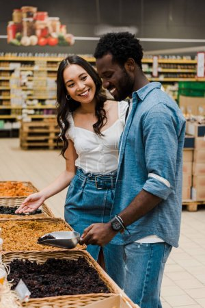 Photo for Happy african american man holding metal scoop with raisins near asian woman gesturing in store - Royalty Free Image