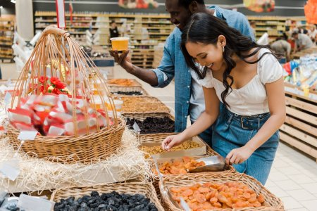 Photo for Happy asian woman looking at dried apricots near cheerful african american man holding honey jar in supermarket - Royalty Free Image