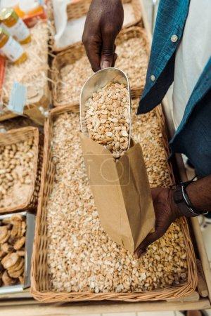 Photo pour Vue recadrée de l'homme américain africain retenant la boule en métal avec les arachides savoureuses en magasin - image libre de droit