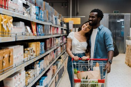 Photo for Happy asian woman standing near cheerful african american boyfriend and looking at shelves with groceries - Royalty Free Image
