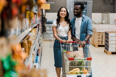 Photo for Selective focus of happy asian woman standing near cheerful african american boyfriend and looking at shelves with groceries - Royalty Free Image