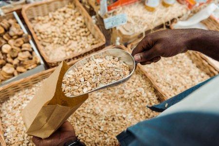 Overhead-Ansicht von afrikanisch-amerikanischen Mann hält Metallschaufel mit leckeren Erdnüssen im Geschäft