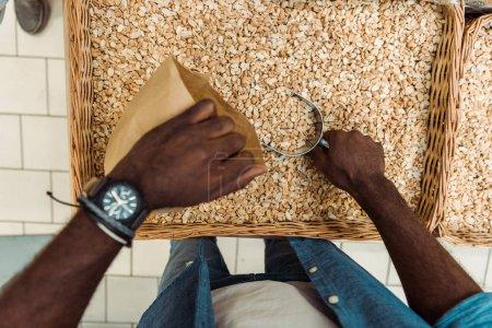 Photo pour Vue supérieure de l'homme américain africain retenant la boule en métal avec les arachides savoureuses près du sac en papier dans le magasin - image libre de droit