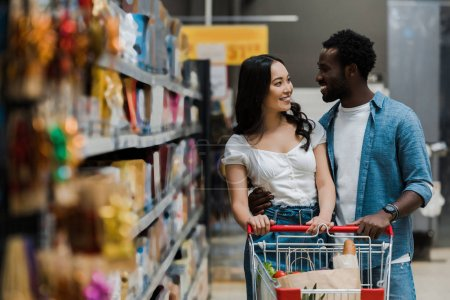 Photo for Selective focus of happy asian woman looking at cheerful african american boyfriend in supermarket - Royalty Free Image